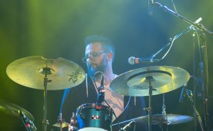 Adam Chase playing drums live on stage
